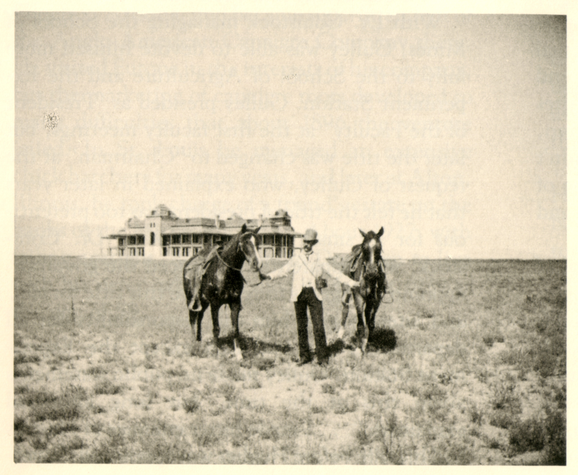 A man with two horses stands in front of Old Main with no other buildings or people in sight