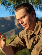 Photo of Bruce Bridges holding a tsavorite gemstone
